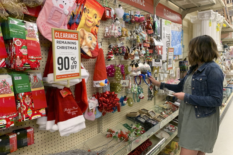 A woman shopping in the Hobby Lobby Christmas clearance section.